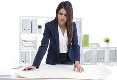 Centered woman architect working with blueprints while standing. Portrait of a centered woman architect working with blueprints in her office. She is standing Royalty Free Stock Image