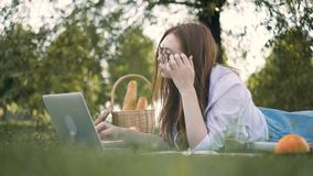 Centered young woman typing at laptop lying on grass in park stock footage