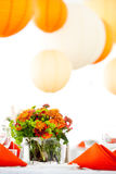 Centerpiece on a table. A green and orange wedding centerpiece on a table Royalty Free Stock Image