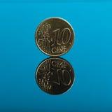 10 centesimi, euro moneta dei soldi sul blu con la riflessione Fotografia Stock Libera da Diritti