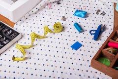 Centimètre, dé, ciseaux et d'autres accessoires de couture sur le morceau de tissu Image stock
