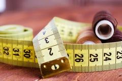 Centimètre de couture et fil sur la table en bois brune Image libre de droits