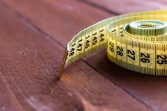 Centimètre de couture sur une table en bois brune Image stock