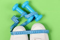 Centimeter in cyan blue color on white trainers and dumbbells. Top view. Sneakers with measuring tape on green background. Fitness and sportswear concept stock photos
