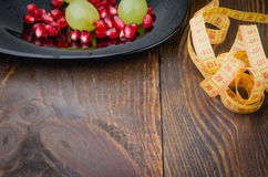 Centimeter, pomegranate and grapes in a plate on a fitness background. Centimeter, pomegranate and grapes in a plate on a wooden background Stock Images