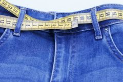 Centimeter tape as belt in jeans close-up, concept of losing weight. Healthy lifestyle. royalty free stock photography