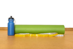Centimeter tape, yoga mat and bottle of water for exercise on yellow  background Stock Image