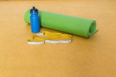 Centimeter tape, yoga mat and bottle of water for exercise on yellow background Stock Photography
