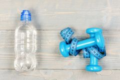 Centimeter tied around sports equipment in cyan blue. On wooden vintage background. Workout and losing weight concept. Tools for healthy lifestyle. Water stock images