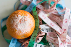 Centimeters sorted randomly and orange Royalty Free Stock Photos