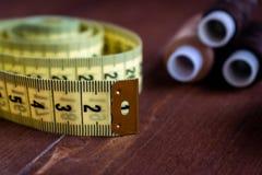 Centimetro di cucito e fili su una tavola di legno marrone fotografie stock