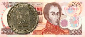25 centimos coin against 5000 venezuelan bolivar bank note stock photo