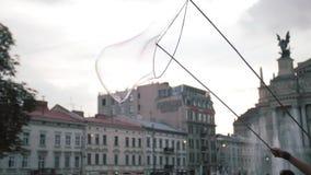 Centinaia di salto di un pagliaccio indipendente di bolle minuscole, piccole e grandi al festival all'aperto nel centro urbano Co video d archivio