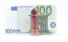 1 centmynt som står av bunt av euro, myntar överst nära sedel för euro 100 Arkivbild