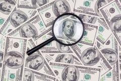 Cento banconote del dollaro sotto la lente d'ingrandimento Fotografia Stock Libera da Diritti