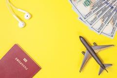 Cento banconote in dollari, aeroplano, cuffie, passaporto straniero su fondo di carta giallo luminoso Copi lo spazio fotografia stock libera da diritti