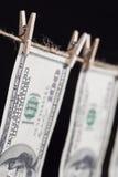Cento banconote in dollari che pendono dalla corda da bucato su fondo scuro Fotografia Stock Libera da Diritti