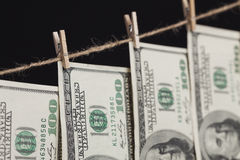 Cento banconote in dollari che pendono dalla corda da bucato su fondo scuro Fotografia Stock