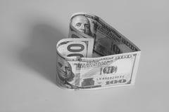 Cento banconote in dollari nella forma del cuore fotografia stock