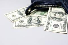 Cento banconote in dollari sono caduto dalla borsa blu scuro delle signore sopra Fotografia Stock