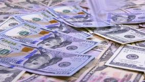 Cento cadute delle banconote in dollari sulla Tabella con i dollari americani delle denominazioni differenti stock footage