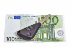 Cento chiavi della banconota e dell'automobile degli euro isolate su bianco Immagini Stock