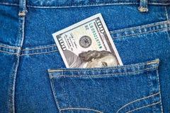 Cento dollari di fattura che attacca dalla tasca dei jeans Fotografia Stock