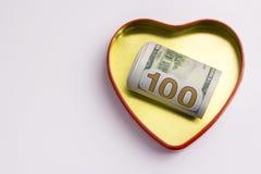 Cento dollari in un cuore dell'oro hanno modellato la scatola con un profilo rosso Concetto per il giorno del ` s del biglietto d immagini stock