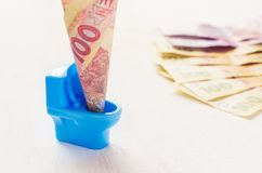 Cento hryvnia dell'ucranino in una toilette blu del giocattolo Immagini Stock Libere da Diritti