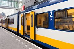 AMSTERDAM, NETHERLAND - JUNE 25, 2017: Yellow Dutch train on the Amsterdam Centraal station platform in morning. Centraal is the largest railway station of Royalty Free Stock Photography