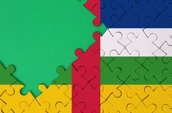Central African Republic flag is depicted on a completed jigsaw puzzle with free green copy space on the left side.  royalty free illustration