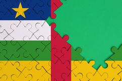 Central African Republic flag is depicted on a completed jigsaw puzzle with free green copy space on the right side.  stock photo