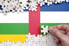 Central African Republic flag is depicted on a table on which the human hand folds a puzzle of white color royalty free stock images