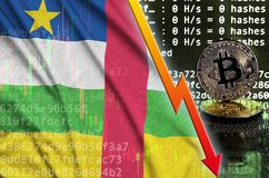 Central African Republic flag and falling red arrow on bitcoin mining screen and two physical golden bitcoins stock photo