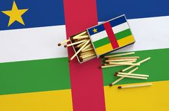 Central African Republic flag is shown on an open matchbox, from which several matches fall and lies on a large flag royalty free stock photo