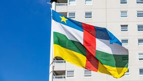 Central African Republic flag waving against clear blue sky. Central African Republic flag. National symbol waving on pole, Highrise building and clear blue sky stock images