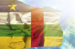 Central African Republic waving flag against blue sky with sunrays royalty free stock photography