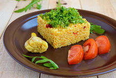Central Asian traditional dish - pilaf (plov risotto) in the form of a square, decorated with chopped parsley. In clay bowl on a light wooden background stock photo