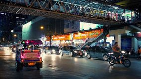 Central Bangkok At Night. Typical scene of Bangkok in the evening with busy road and people passing overhead on footbridge stock footage