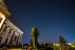 Central building of count Potocki palace, Tulchyn, Vinnytsia region, Ukraine, on a warm spring night against clear dark blue sky. Rear side of the central royalty free stock image