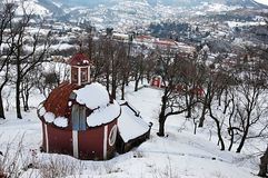 Central church of calvary in Banska Stiavnica covered with snow, view from upper chapels path during winter 2018. Afternoon partly cloudy weather Stock Image