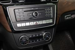 The central control console on the panel inside the car close-up with climate control and audio system and a hole for the CD and. Emergency button in gray and stock images