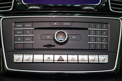The central control console on the panel inside the car close-up with climate control and audio system and a hole for the CD and. Emergency button in gray and stock image