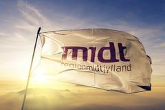 Central Denmark Region flag textile cloth fabric waving on the top sunrise mist fog. Beautiful stock photography