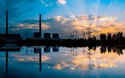 Central eléctrica de energía del carbón en la puesta del sol y la reflexión en agua Imágenes de archivo libres de regalías