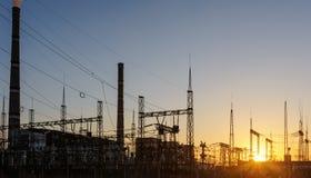 Central eléctrica de energía del carbón en la puesta del sol y la reflexión en agua Imagen de archivo libre de regalías