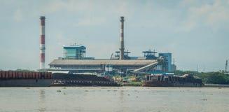 Central eléctrica de energía del carbón en riverbank con la gabarra llena de carbón en el muelle indonesia fotografía de archivo