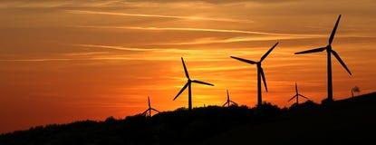Central eléctrica de energía eólica en las montañas en la puesta del sol Foto de archivo libre de regalías