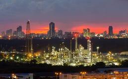 Central eléctrica de la refinería con el fondo de la ciudad en el centro de la ciudad durante puesta del sol Imagen de archivo