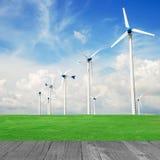 Central eléctrica del molino de viento en planta verde del campo y de madera contra azul Imagenes de archivo